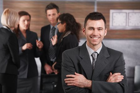 Happy businessman standing in office in front of business team. photo