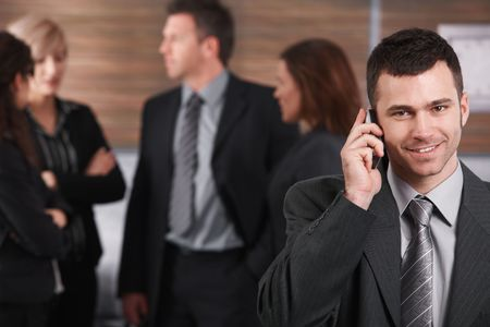 Portrait of young businessman talking on mobile phone, smiling, business people in background. photo