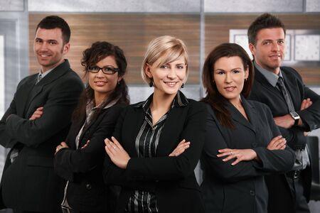 Équipe de gens d'affaires heureux succès permanent dans le bureau, femme d'affaires en face souriante.