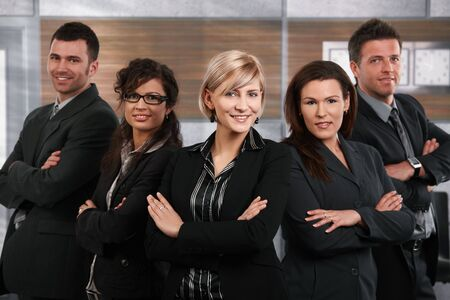 employee satisfaction: Team of successful happy businesspeople standing in office, businesswoman in front smiling.
