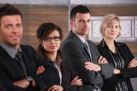 Portrait of businesswoman and team standing in a row on office corridor, smiling. photo