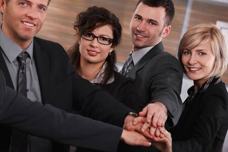 Portrait of happy successful businesspeople joining hands, looking at camera, smiling. photo