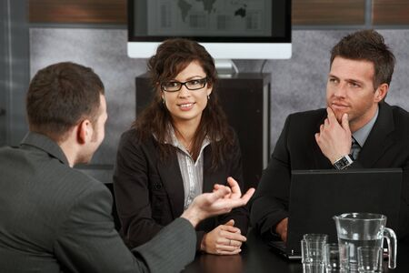 Young businesspeople having a meeting at table in office, discussing work, smiling. photo