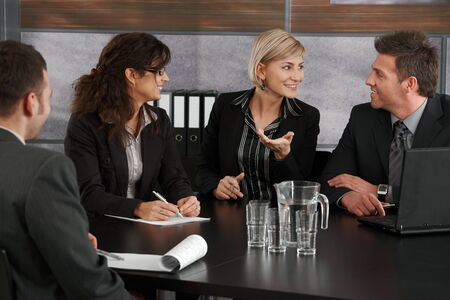 group communication: Young businesswoman explaining business problem, sitting at meeting table in office, others looking at her.