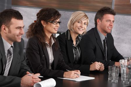 Attractive young businesswoman sitting at table on business seminar together with colleagues, looking at camera, smiling. photo