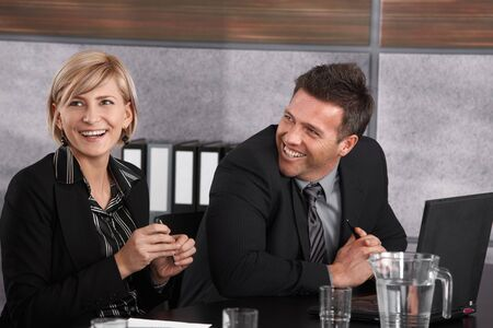 Happy business partners working in office, laughing. photo
