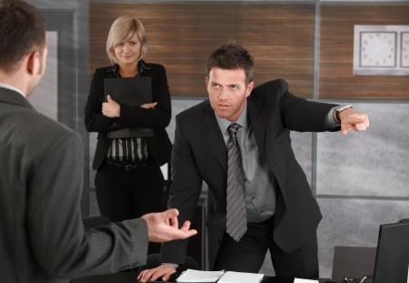 argument: Cottura esecutivo dipendente in ufficio, che punta fuori della cornice.