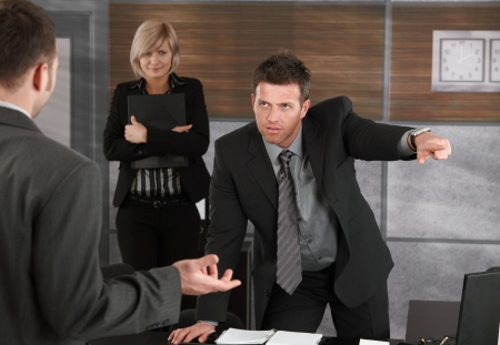 disgrace: Executive firing employee in office, pointing out of frame.