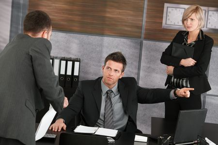 disgrace: Businessman trying to explain himself to disappointed executive showing the door. Stock Photo