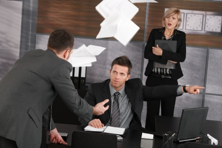 jefe enojado: Empleado de disparo de jefe enojado, mostrando la puerta. Papeles volando en el aire, Secretario de miedo permanente en segundo plano. Foto de archivo