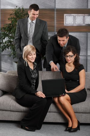 Young businesswomen sitting at couch in office holding laptop computer, businessman showing someting on screen. photo