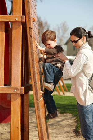 jungle gyms: Mother helping little boy to climb wooden climbing wall on playground, sunlit outdoor.