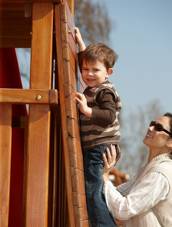 helping people: Happy mother helping little boy to climb wooden jungle gym on playground, sunlit outdoor. Stock Photo