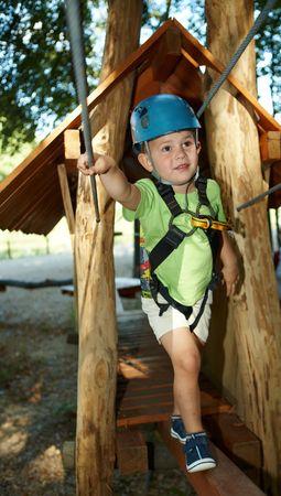 Little boy having fun in adventure park wearing mountain helmet and safety equipment.  photo