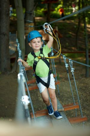 safety harness: Little boy having fun in adventure park wearing mountain helmet and safety equipment.