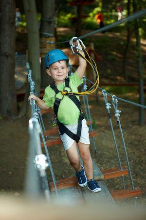 bonne aventure: Petit garçon amusant dans le parc aventure portait la montagne casque et la sécurité des équipements.  Banque d'images