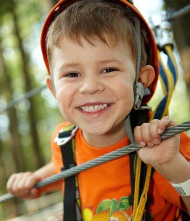 Portrait de joyeux petit garçon amusant dans le parc aventure sourire à porter la montagne casque et la sécurité des équipements de caméra.  Banque d'images