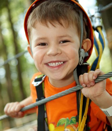 Portrait of happy little boy having fun in adventure park smiling to camera wearing mountain helmet and safety equipment. photo