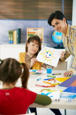 Teacher and elementary age schoolgirl showing colorful paining to classmate in art class in primary school classroom. photo