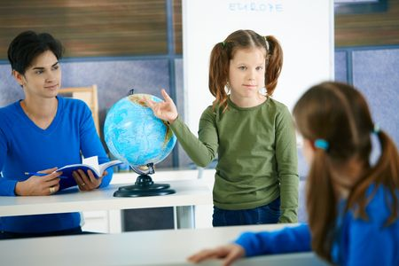 Young schoolgirl pointing at globe in class, looking at another pupil, teacher smiling. photo