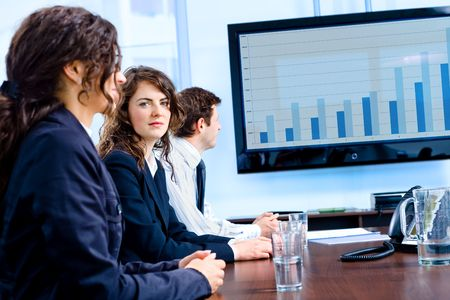 Team of happy young businesspeople having meeting in boardroom at office in front of a huge plasma TV screen, indoor, smiling. Stock Photo - 6726321