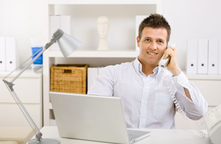 Casual businessman working at home using laptop computer, talking on phone. photo