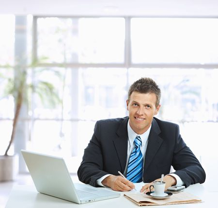 businesspersons: Businessman sitting at table in office lobby, writing note on paper.