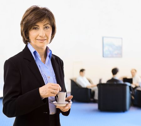 Senior businesswoman drinking coffee, standing in office lobby. photo