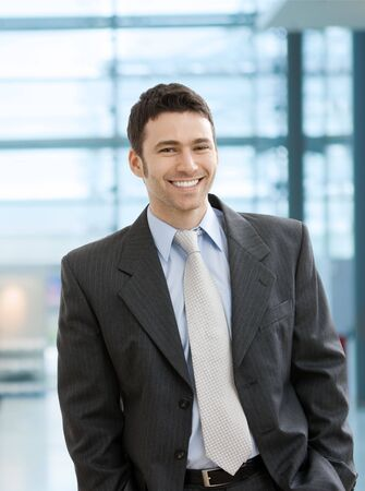 Happy businessman standing with hands in pocket in office lobby, looking at camera, smiling.  photo