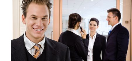 Happy businessman smiling in front, other businesspeople talking in the background. Stock Photo - 6726481