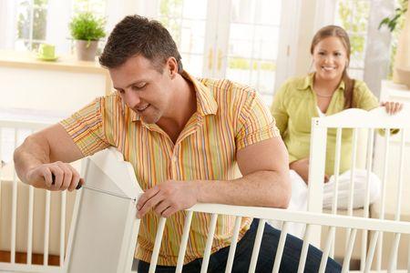 werkende moeder: Lachende vader zich te concentreren op de vaststelling van baby bed thuis, vrouw die lacht in de achtergrond.