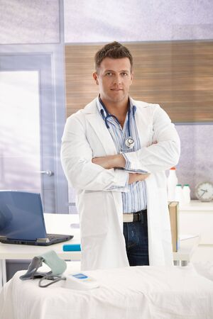 Mid-adult doctor standing in consulting office at desk with arms folded, looking at camera. photo