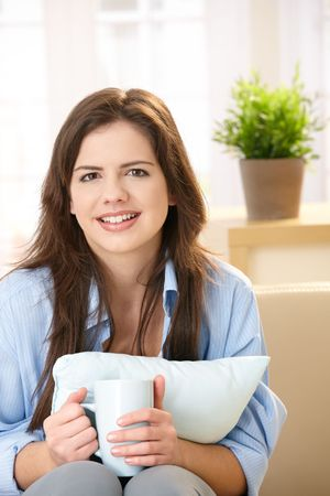 Portrait of attractive young woman drinking morning coffee sitting on sofa with pillow, smiling at camera. photo