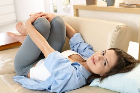 Young woman smiling at camera, lying on sofa at home with feet pulled up, hands around knees. photo