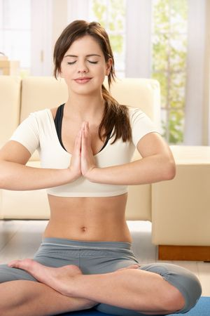 Girl doing yoga meditation sitting on living room floor with closed eyes, smiling. photo