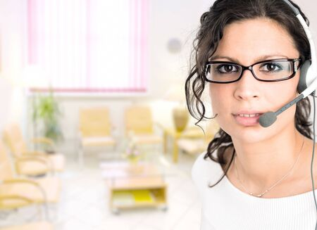 Young female receptionist at clinic reception talking on headset. Stock Photo - 6726329
