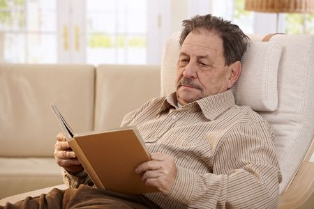 Senior man resting in chair at home, reading book. photo