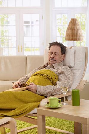 Senior man lying in armchair, fell asleep while reading book. photo
