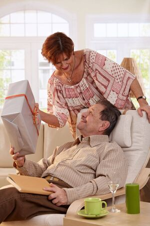 Elderly couple celebrating birthday. Wife giving present to her husband, surprising him from behind. photo