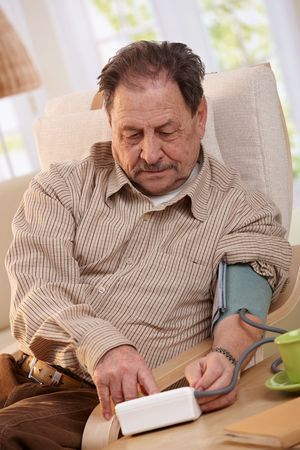 Elderly man using blood pressure meter at home.  Stock Photo - 7136686