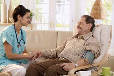 care at home: Nurse measuring blood pressure of senior man at home. Smiling to each other. Stock Photo