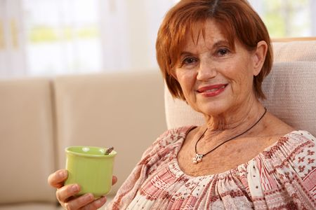 Portrait of happy senior woman sitting in chair at home drinking coffee, smiling. photo