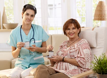 Nurse and senior patient drinking coffee after examination at home, smiling.   photo