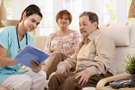 buena salud: Enfermera hablando con las personas mayores y haciendo notas durante el examen en casa, sonriendo.