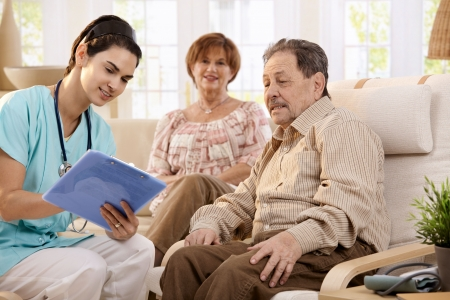 Nurse talking with elderly people and making notes during examination at home, smiling. Stock Photo