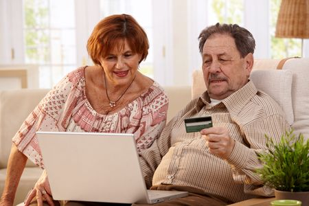 Elderly couple shopping online at home, using laptop computer and credit card.