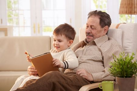 two story: Grandfather sitting in armchair and reading tales to grandson.
