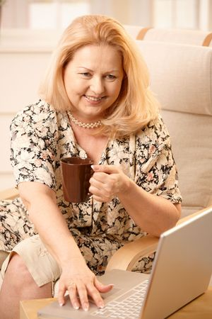 Senior woman drinking coffee, looking at laptop computer with big smile, typing. Stock Photo - 6746159