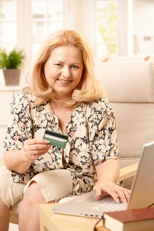 creditcard: Senior woman smiling at camera while shopping online, holding creditcard and typing on computer keyboard.