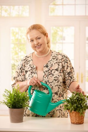 Portrait of smiling mature woman watering potted plants from can, looking at camera, smiling. Stock Photo - 6746110